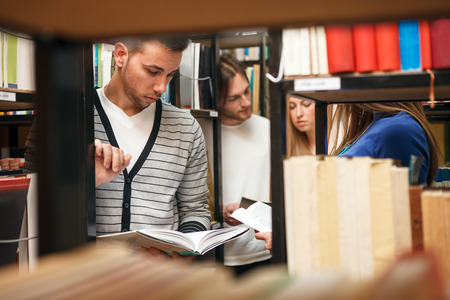 university classroom: Students in library choosing books Stock Photo