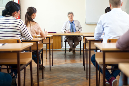 high class:  Teacher sitting in classroom full of students during class