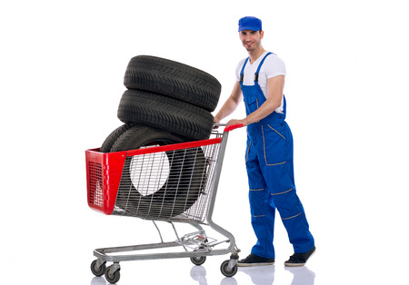 Young mechanic pushes full shopping carts of tires for the car photo