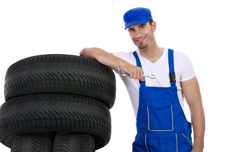 Young mechanic with tires and wrench, isolated over white photo