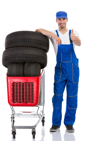 Young mechanic with tyre giving a thumbs up photo