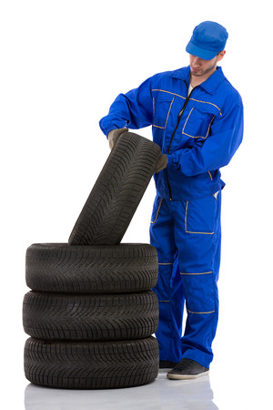 winter tyre: Young motor mechanic with  a tyre Stock Photo