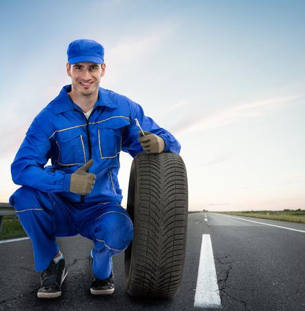 Jong Lachend monteur zien thumbs up naast autobanden - weg bijstand, Sleepdienst Stockfoto