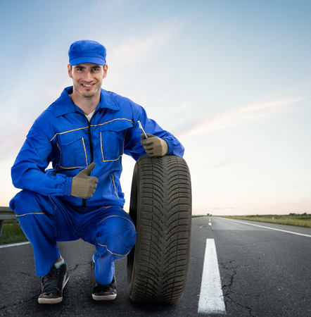 road assistance: Young Smiling mechanic showing thumbs up next  car tires - road assistance, Towing Service