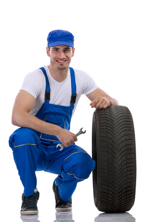 Friendly car mechanic with  tires and wrench Stock Photo