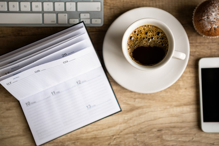 Wooden desk with coffee cup and office supplies photo
