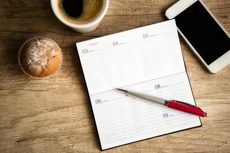 労働時間を計画、木製の机の上のノートブックを開く