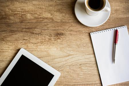 tabla de surf: Lugar de trabajo con tableta en blanco digital, papel, bolígrafo y una taza de café en la mesa de trabajo. Sobre la opinión tiro. Foto de archivo