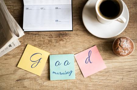 Goede morgen op het werk van een kopje koffie op houten bureau Stockfoto