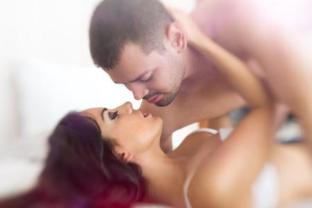 sexo pareja joven: j�venes amantes que se besan en la cama Foto de archivo
