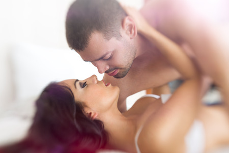 sex activity: young lovers kissing in bed