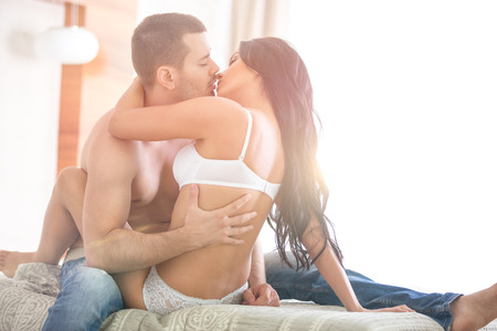 sex couple: young passion lovers kissing on bed Stock Photo