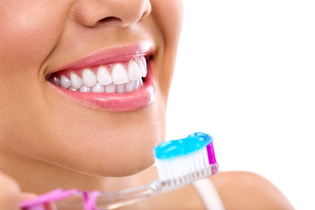 dientes: Mujer joven sonriente con los dientes sanos sosteniendo un cepillo de dientes Foto de archivo