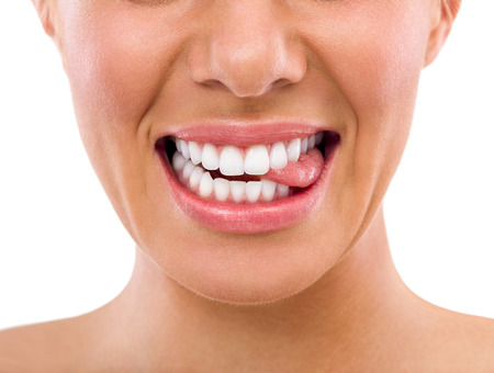oral care: Female biting tongue with perfect white teeth