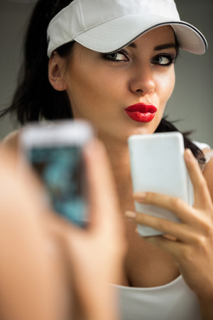 selfie - girl making self portrait with a phone front of the mirror photo
