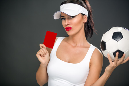 misdemeanor: Sexy attractive woman giving red card and holding soccer ball Stock Photo