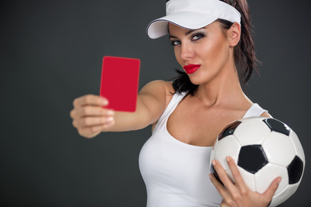 misdemeanor: Young attractive woman with a soccer ball showing  red card Stock Photo
