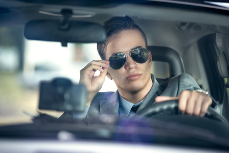 business man with sunglasses  driving a car photo
