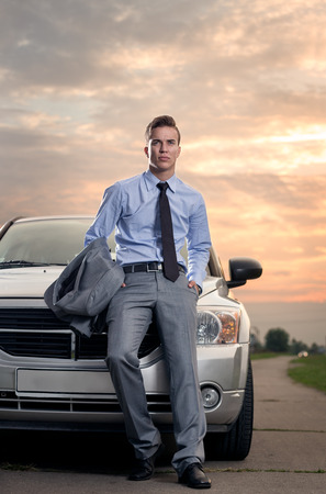 pose: Handsome young man leaning on his car. Attractive gorgeous guy standing, outdoors - outside Stock Photo