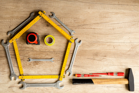 Funny construction background of different tools on the wood plank photo