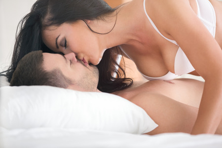 nude in bed: love kiss of young sexy heterosexual sensual couple