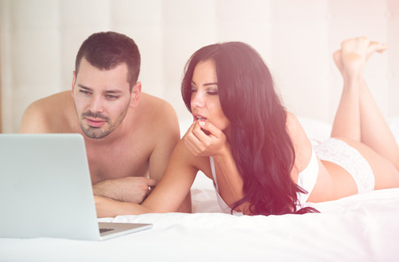 happy young couple: Young couple with laptop in bed
