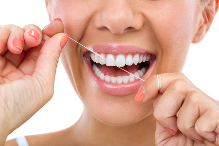 flossing: Young woman flossing her teeth , close up , isolated on white background