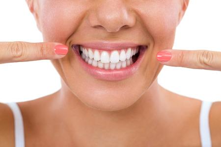 Žena ukazuje její dokonalé rovné bílé zuby.