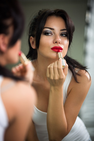 Woman doing make-up, beautiful young woman doing make-up and smiling while looking at the mirror photo