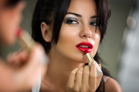 Young woman applying lipstick looking at mirror photo