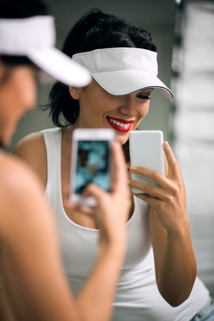 attractive girl with a phone in front of the mirror, making picture photo