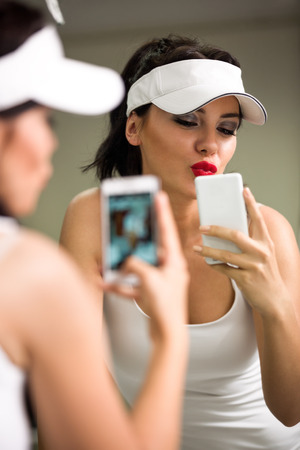 attractive girl having fun with a phone in front of the mirror, making picture photo
