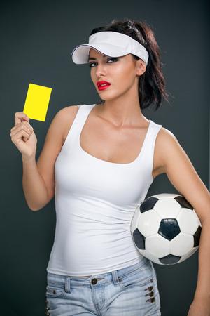 arbitro: Atractivo árbitro de fútbol árbitro de fútbol femenino castiga con una tarjeta amarilla