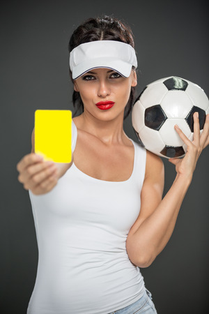 Mujer con el árbitro balón de fútbol con la tarjeta amarilla Foto de archivo - 32893964
