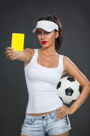 misdemeanor: attractive girl with a soccer ball showing  yellow card