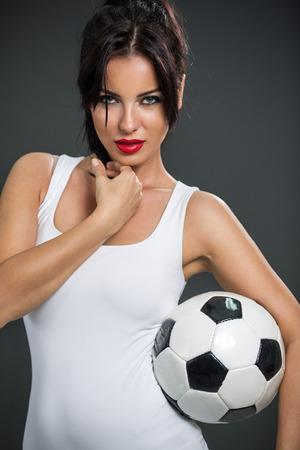 seductive woman posing with soccer ball, looking at camera photo