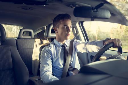Elegante jonge positieve man in de auto buiten Stockfoto