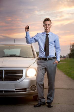 llave de sol: Hombre hermoso sonriente sosteniendo claves del nuevo coche Foto de archivo