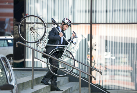 businessman with a cycle helmet on head carrying his bike down steps Stock Photo