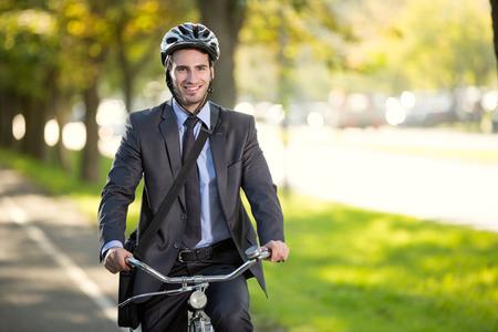 lachende jonge zakenman rijdt op een fiets naar het werk, concept gas besparingen concept