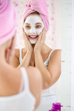 mirror face: Young  woman applying facial cleansing mask, beauty treatments