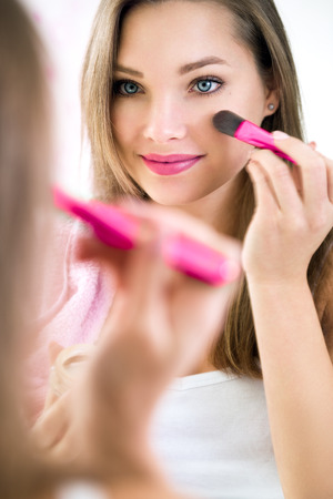 feminine beauty: Reflection of young beautiful woman applying her make-up, looking in a mirror Stock Photo
