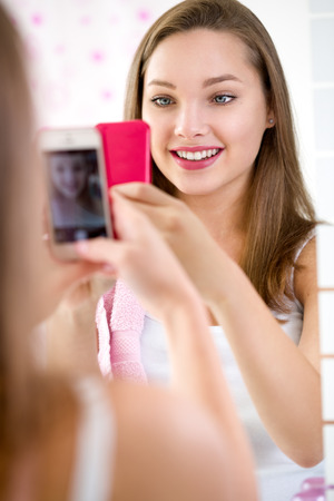making faces: Beautiful teen girl making self-portrait front mirror in bathroom Stock Photo