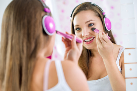 cute teen girl: Teen girl in bathroom makeup and listening to music