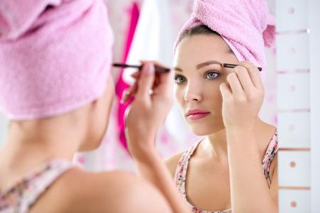 beatification: Young woman  with long eyelashes and mascara brush Stock Photo