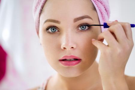 mujer maquillandose: Cerca de la hermosa mujer joven que aplica el rimel