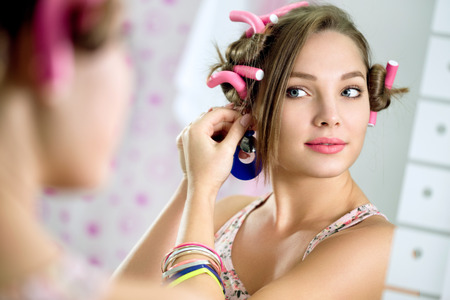 hair curlers: Young  girl with hair curlers in hair standing front  the mirror puts earring Stock Photo