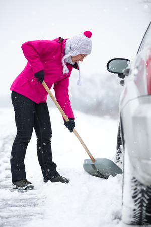 shoveling: Woman  shoveling and removing snow from his car during a snowing