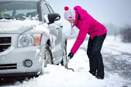 シャベルおよび除雪雪で立ち往生している、彼女の車からの女性 写真素材