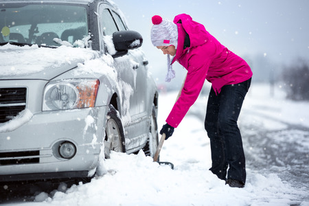 woman shoveling and removing snow from her car, stuck in snow Stockfoto